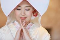 綿帽子と刺繍襟に白無垢合わせたコーディネートで和装の婚礼前撮り写真を撮る新婦の写真