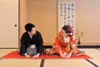 掛け軸と畳のある和室で赤い敷物の上で正座をしてあいさつをする和装の婚礼前撮りの新郎と赤い色打掛の新婦