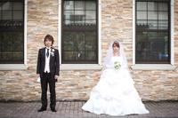 タキシードとウェディングドレスを着て並ぶ新郎新婦のウェディングフォト
