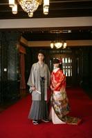 旧前田侯爵邸の赤絨毯とシャンデリアと寄り添うグレーの紋付き袴を着た新郎と赤い色打掛を着た新婦の和装婚礼前撮り写真