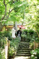 新緑のきれいな日本庭園で和装の婚礼前撮りをする赤い番傘を持つ新郎と白無垢の新婦