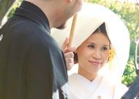 東京の日本庭園で、やわらかい自然光の中、和装の前撮り写真を撮る新郎と、綿帽子に白無垢姿の新婦