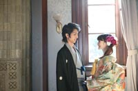 旧前田侯爵邸の自然光の入る居室で見つめあう和装の新郎と緑の色打掛にダウンスタイルの似合う新婦の和装の婚礼前撮り写真