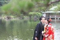 東京の大きな池のある日本庭園で、仲良くカジュアルな雰囲気の写真を撮る和装の新郎と赤い色打掛の新婦のフォトウェディング