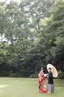 新緑のきれいな季節に旧細川侯爵邸の中庭で和装の婚礼前撮り写真を撮る白い和傘を持つ新郎と赤い色打掛の新婦