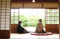 和装の婚礼前撮りで新緑の季節に和室で中庭をみてくつろぐ新郎と緑色の色打掛を着た新婦