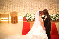 チャペルでウェディングフォトを撮る、タキシードを着た新郎とウェディングドレスの新婦の誓いのキス