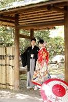旧古河庭園の日本庭園部分で、和傘を使ったフォトウェディングと撮る和装の新郎と赤い色打掛を着た新婦