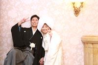 旧前田侯爵邸の豪華な壁紙の前で自然な表情でウェディングフォトを撮る和装の新郎と綿帽子と白無垢姿の新婦