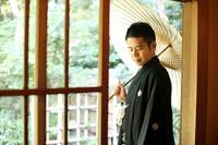 和装の婚礼前撮りで日本庭園とお茶室を利用した和傘を持つ黒紋付き袴の新郎の一人の写真