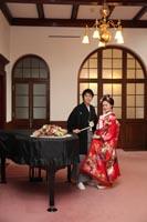 旧古河庭園洋館のエントランスで、並んで立つ和装の新郎と日本髪に赤い色打掛を着た新婦のフォトウェディング