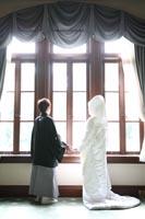 旧前田侯爵邸の居室で逆光の中に手をつないで立つ和装の新郎と綿帽子と白無垢姿の新婦の後ろ姿のウェディングフォト
