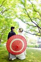 東京の日本庭園で、新緑の季節に、緑に囲まれながら赤い和傘をさして、楽し気に写る和装の新郎と白無垢姿の新婦のフォトウェディング