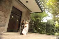 旧細川侯爵邸の車止めで向かい合う洋装の新郎と白無垢姿の新婦のフォトウェディング