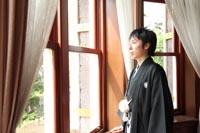 旧古河庭園洋館の自然光の入る居室で、窓際に立ち外を眺める、和装の新郎の婚礼前撮り写真