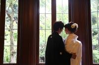 旧前田侯爵邸の大きなガラス窓の近くで和装の婚礼前撮り写真を撮る新郎と白無垢姿の新婦の後ろ姿