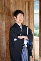 東京の日本庭園で、黒紋付き袴を着てポーズを決める新郎の、和装のフォトウェディング写真