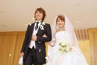 チャペルでフォトウェディングを挙げる、タキシードを着た新郎とウェディングドレスの新婦のフラワーシャワーでの退場シーン