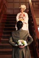 旧細川侯爵邸の大階段で生花ブーケを持ち告白しようとする洋装の新郎と白無垢姿の新婦のフォトウェディング