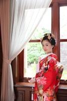 旧古河庭園洋館の自然光の入る居室の窓際に立つ、日本髪と赤い色打掛の新婦の和装前撮り婚礼写真