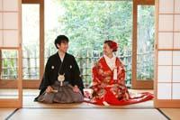 新緑の季節に和室で和装で結婚式の前撮りをする仲良く正座する新郎と赤い色打掛の新婦