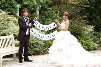 チャペルでフォトウェディングを挙げる、新郎新婦が、ガーランドを持って記念撮影