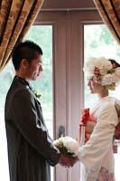 旧細川侯爵邸で向かい合う洋装の新郎とお花がたくさんついた髪飾りの白無垢姿の和装と洋装の婚礼前撮り写真