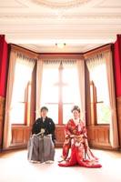 旧古河庭園洋館の自然光の入る赤い喫茶スペースで、椅子に座ってフォーマルな写真を撮る、和装の新郎と赤い色打掛の新婦のフォトウェディング