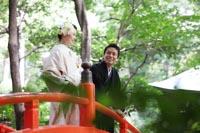 東京の赤い橋のある日本庭園で、新緑の季節に、カジュアルな雰囲気のフォトウェディングを撮る和装の新郎と白無垢姿の新婦