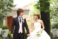 新緑の季節にウェディングドレスとタキシードを着て、ウェディングフォトを撮る新郎新婦