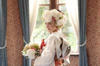旧細川侯爵邸の青いカーテンのある居室で生花のブーケを持ち振り向くお花のヘア飾りが豪華な白無垢姿の新婦の和装の婚礼前撮り写真