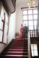 旧古河庭園洋館の自然光の入る階段の踊り場で、フォーマルな構図の写真を撮る和装の新郎新婦のフォトウェディング