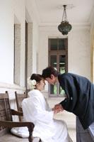 旧前田侯爵邸のテラスのベンチに座る白無垢姿の新婦と手をつなぐ和装の新郎の婚礼前撮り写真