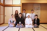 和装の婚礼前撮りをする正座している黒紋付きの新郎と綿帽子と白無垢の新婦と正座する両家の親族の家族写真
