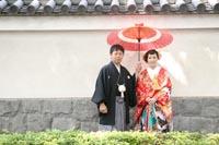 東京の日本庭園で、お城の城壁のような壁のある場所で赤い和傘を持って、仲良く並ぶ和装の新郎と赤い色打掛の新婦のカジュアルなウェディングフォト