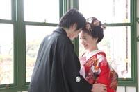 旧古河庭園洋館の自然光の入るサンルームで、見つめあう和装の新郎と、日本髪に赤い色打掛の新婦の婚礼前撮り写真