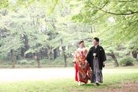 旧前田侯爵邸と新緑の美しい駒場公園で散歩しているようなナチュラルな婚礼前撮り写真を撮る和装の新郎と赤い色打掛の新婦