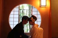 和装の婚礼前撮りをする丸い窓、悟りの窓の前で正座をする新郎と白無垢姿の新婦