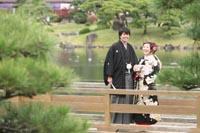 東京の日本庭園で、池が見える橋の上に立つ和装の新郎と黒引き振袖を着た新婦のカジュアルな前撮り写真
