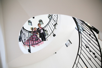 チャペルでウェディングフォトを撮る、螺旋階段の上にいる、タキシードを着た新郎とカラードレスの新婦