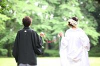 旧前田侯爵邸から新緑の美しい駒場公園を見ている赤い糸の小道具を持つ和装の新郎と白無垢姿の新婦の後ろ姿のフォトウェディング