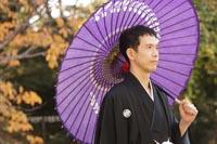 東京の日本庭園で、紅葉の季節に、紫色の和傘を持つ黒紋付き袴の新郎のウェディングフォト