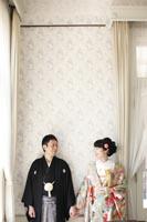 旧古河庭園洋館の自然光の入る明るい白い部屋でカジュアルな雰囲気で写る和装の新郎と緑色の打掛を着た新婦の婚礼前撮り写真