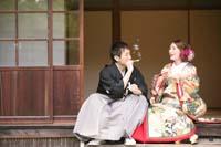 和装で婚礼前撮りをする縁側でシャボン玉を服黒紋付きの新郎と深緑色の色打掛を着た新婦