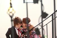 チャペルでウェディングフォトを撮るカジュアルなタキシードの新郎とピンクのカラードレスを着た新婦