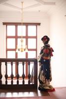 旧古河庭園洋館のシャンデリアとステンドグラスが見える場所で逆光の中に立つ黒引き振袖を着た新婦のドラマチックなフォトウェディング