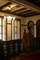 旧前田侯爵邸のシャンデリアが見える場所で向かい合う新郎と色打掛の新婦の和装の婚礼前撮り写真