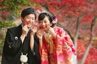 東京の日本庭園で、紅葉の季節に、もみじを両手に持ちカジュアルなウェディングフォトを撮る和装の新郎新婦