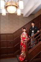 旧細川侯爵邸のエントランスにある階段でたたずむ新郎と赤い色打掛を着た新婦の和装の婚礼前撮り写真