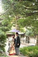 旧前田侯爵邸の日本庭園で和傘を持つ新郎と緑色の色打掛を着た新婦の和装の婚礼前撮り写真